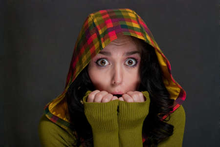 beauty scared girl in hood of tattersall on the gray background