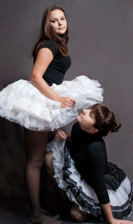 superiority: two beauty ballerina in black and white tutu on grey background Stock Photo
