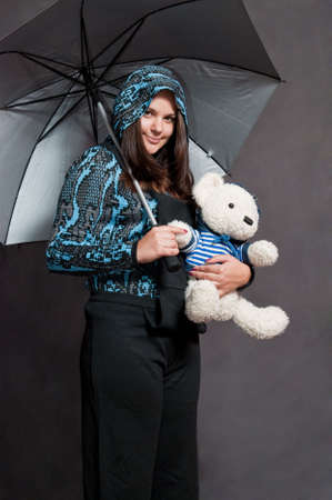 beauty girl in black overalls with bear on the gray background photo