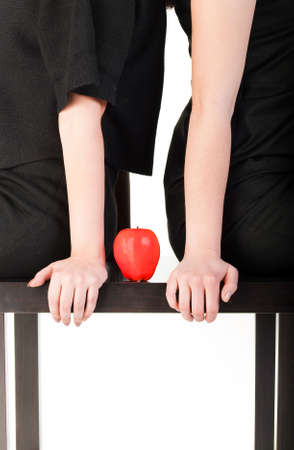 red apple on black wood table between two girl  isolated on white background photo