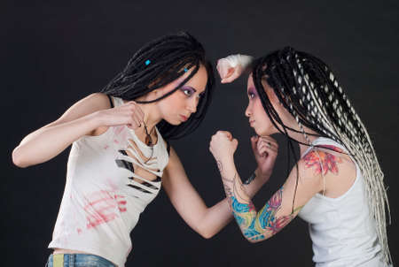 dreads: white fighting girls with dreads on black background. One girl with body art on her hand. Stock Photo