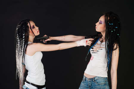 two white girl with handguns  on black background photo