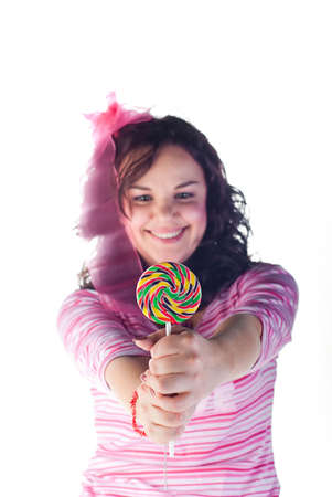 beauty girl looks on colorful lollipop isolated on white background photo