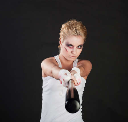 white girl fighter with baseball bat on black background photo