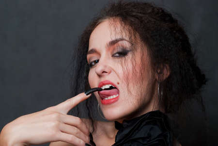 beauty young witch touches tongue black nail on gray background photo