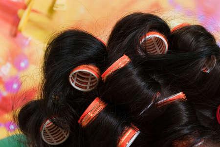 hair rollers: rodillos de pelo de mujer en el fondo de color
