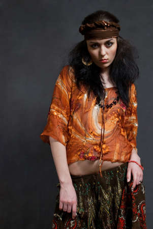 tired young Gypsy woman on the gray background photo