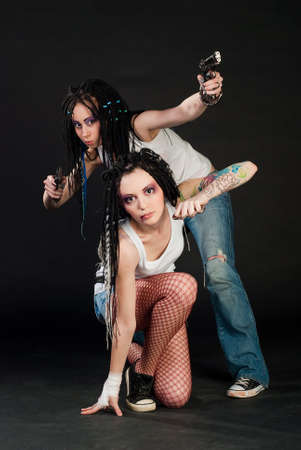 two white girl with handguns on black background. One girl with body art on her hand. photo