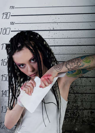 white girl in prison with injuries and body art on her arm tear blank on ruler background photo