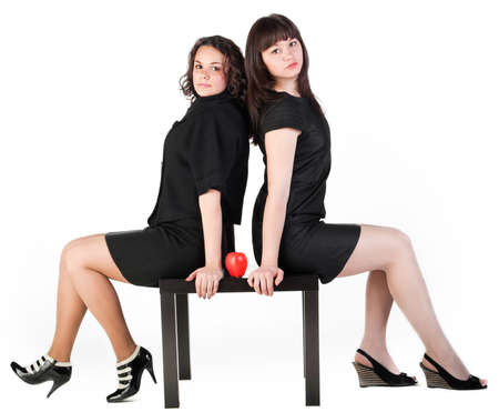 red apple on black wood table between two girl on white background photo