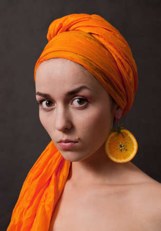 beauty girl with orange headscarf and fruit earring on gray background photo