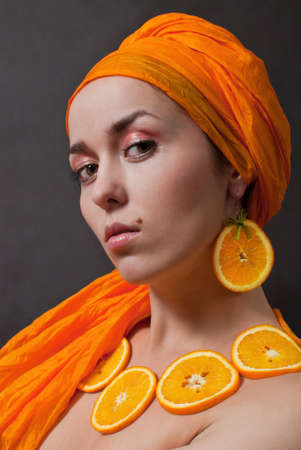 head shot: beauty girl with orange headscarf and fruit necklace on gray background Stock Photo