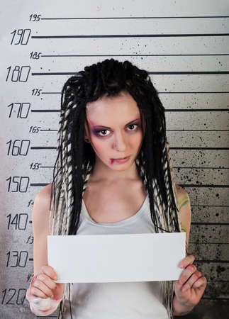 white girl in prison with injuries and body art on her arm on ruler background photo