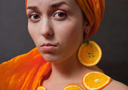 beauty girl with orange headscarf and fruit necklace on gray background photo