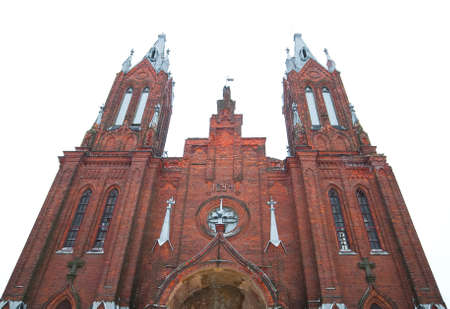 catholicity: ancient Catholic cathedral of red brick on sky background