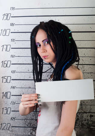 angry white girl in prison with injuries on ruler background photo