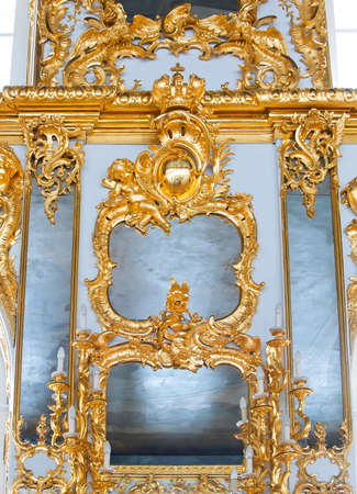 molding: mirrors in frames with golden decorations on wall