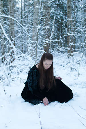 beauty girl in black dress sit in winter forest photo