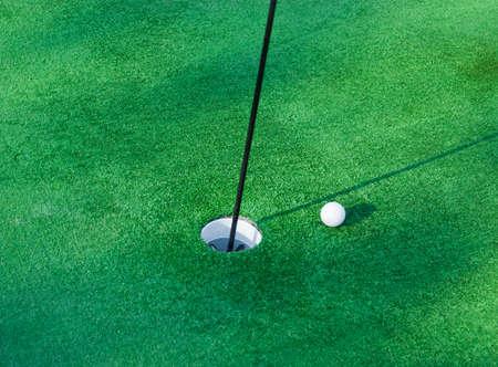 ball near hole on a mini-golf course Stock Photo - 12377444