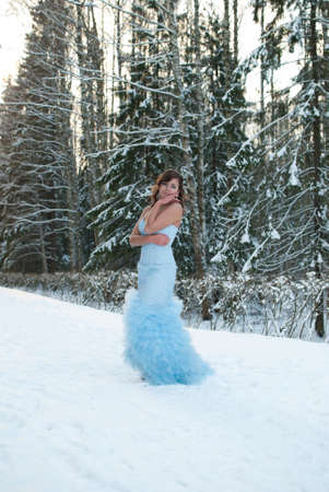 beauty girl in blue dress in winter forest photo