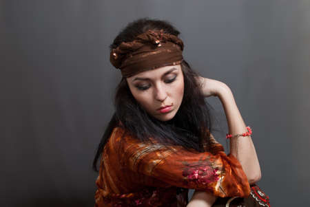 gipsy: beauty young Gypsy woman on the gray background