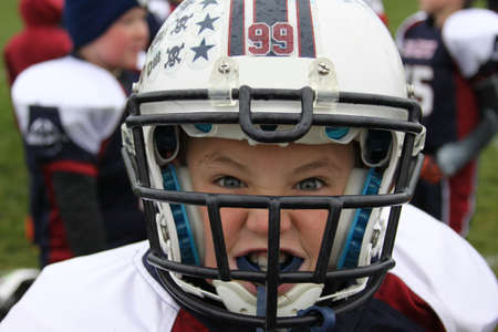 football tackle: Youth football player in helmet and pads making game face