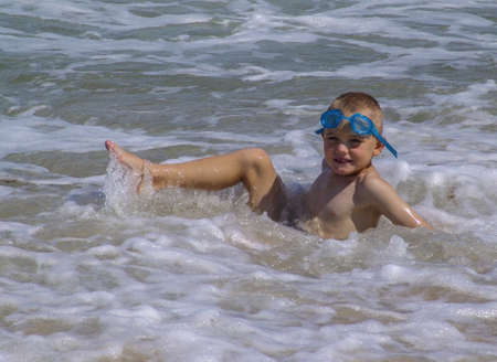 A little boy playing in the ocean with blue goggles
