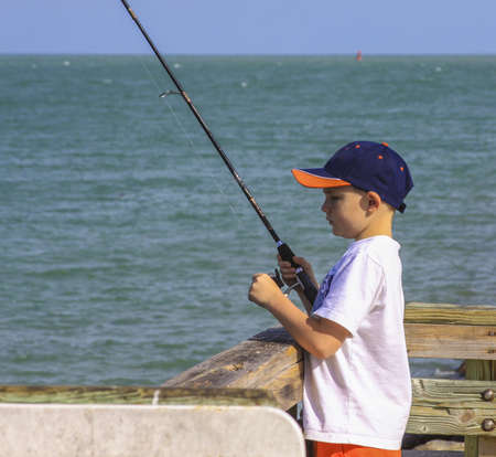 A little boy fishing in the ocean wearing baseball cap.