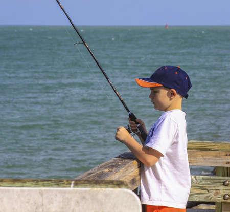 A little boy fishing in the ocean wearing baseball cap. Stock Photo - 21144295