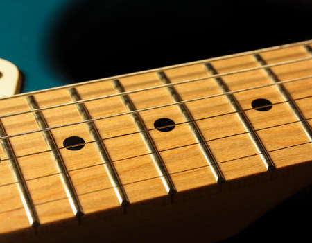 Detail of an electric guitar fretboard on a black backgound Stok Fotoğraf