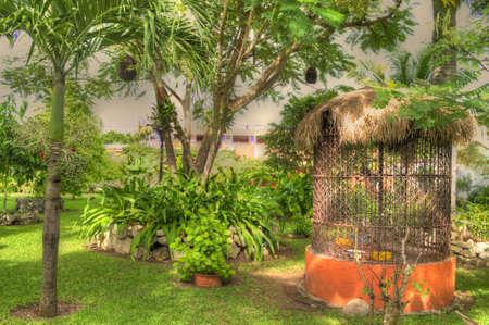 A birdcage in a lush green garden.