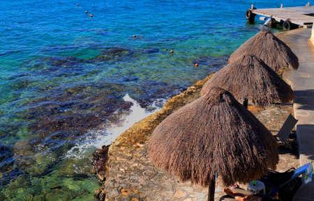 カリブ海の海の端にいくつかの palapas の写真。