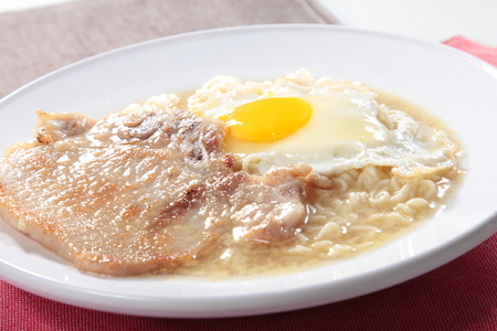 A cuisine photo of pork chop noodles with egg