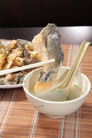 Smakelijke gefrituurde zalmhuid geserveerd op een bord
