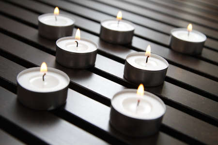 Tea lights on a wooden bench Stock Photo