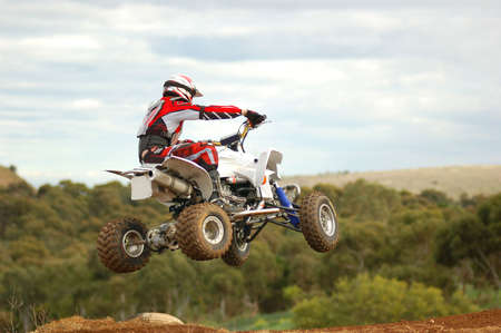 Quad bike racer jumping into corner away from camera photo