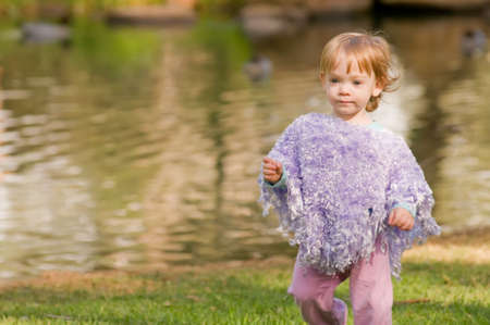 Young toddler playing outside by a pond photo