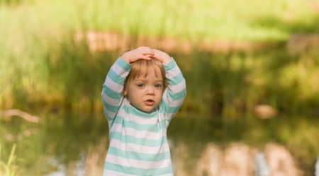 Young girl with arms over head in surprise photo