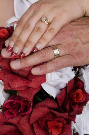 Couples ring hands over the bridal bouquet Stock Photo - 10483313