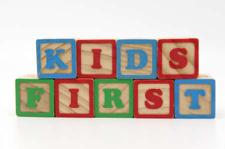 in custody: Wooden blocks spelling kids first, conceptual idea that childrens best interest should be in mind when dealing with separation and divorce
