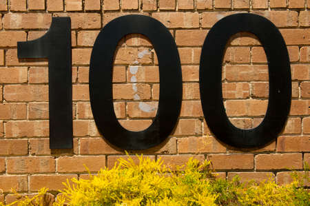 identifier: The number 100 on a brick wall Stock Photo