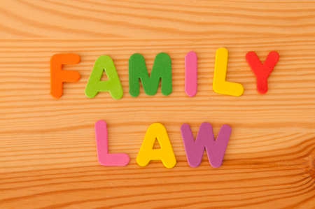 Foam letters spelling out Family Law on a wooden background