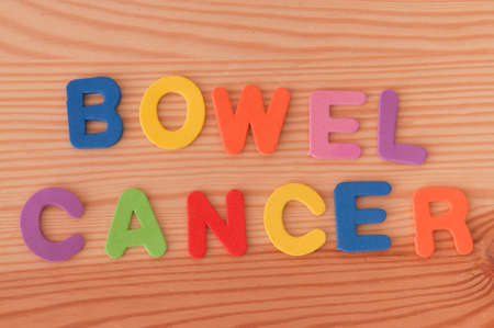 bowel: The words bowel cancer made from foam letters on a wooden background