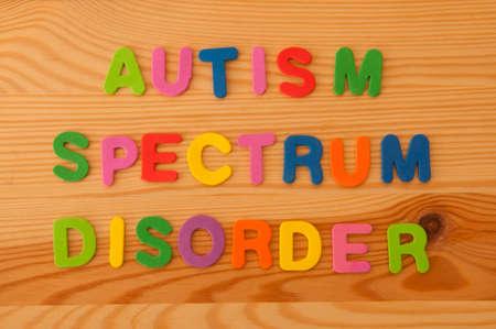 trastorno: Letras de espuma coloridos que explican el trastorno del espectro autista en un fondo de madera