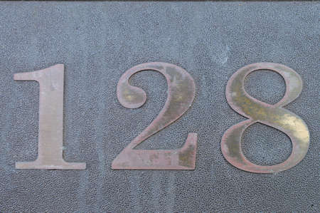 affixed: The number 128 affixed to a building exterior Stock Photo