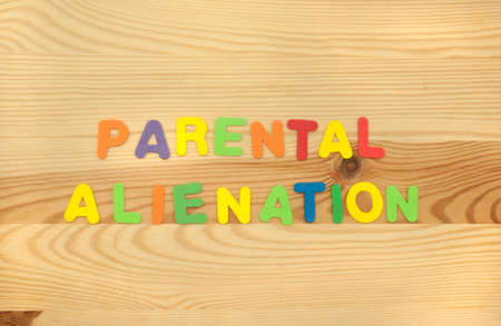 The Term Parental Alienation made from foam alphabet letters on a wooden background