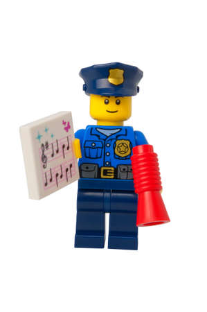 carols: ADELAIDE, AUSTRALIA - September 11 2014:A studio shot of a Policeman holding carols sheet Lego minifigure issued in the 2014 Lego Advent Calendar. Lego is extremely popular worldwide with children and collectors.