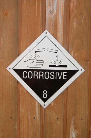 corrosive: Corrosive warning sign on a wooden background