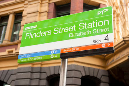 flinders: Melbourne, Australia - August 29, 2014: A Flinders Street Station sign on the streets of Melbourne. Flinders street Station is the main transport hub in the city of Melbourne linking train,bus and tram services throughout the city.