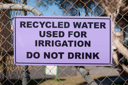 recycled water: A purple recycled water warning sign attached to a fence Stock Photo